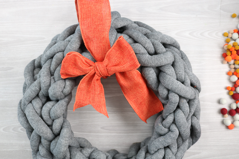 adding bow to yarn wreath