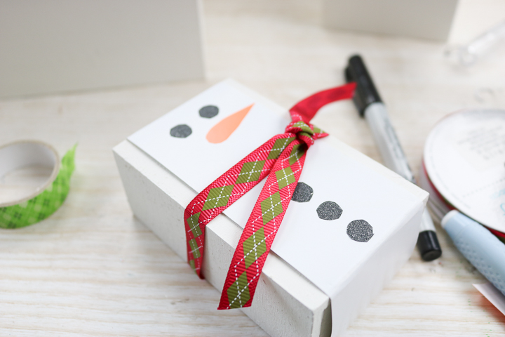 adding ribbon to a gift box