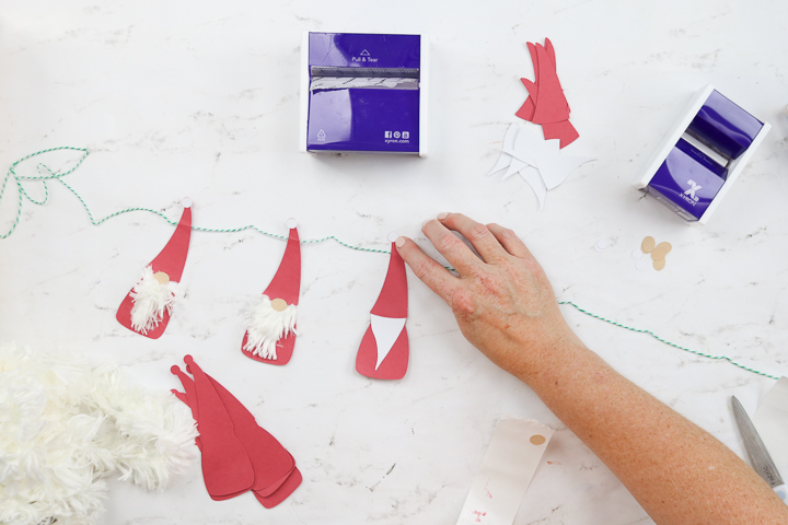 adding ball to hat on a paper christmas gnome