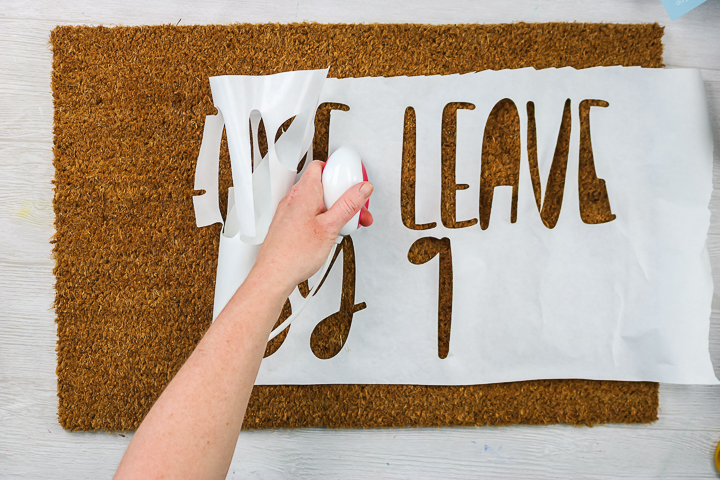 applying freezer paper stencil to a doormat