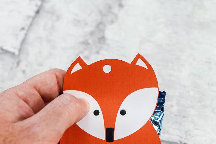 punching a hole in the top of a gift bag