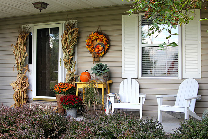 Fall front porch with fall wreath, corn stalks, yellow table with pumpkin and mums.