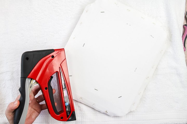 adding staples to add canvas to frame