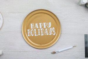 adding vinyl happy holidays to pizza pan wreaths