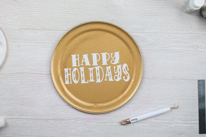 adding vinyl happy holidays to pizza pan wreaths
