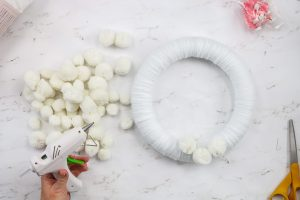 using hot glue to secure white pom poms to a wreath