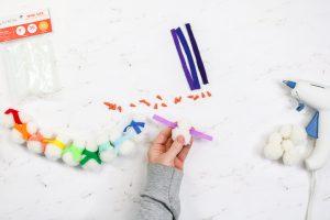 adding a felt scarf to a snowman made from pom poms