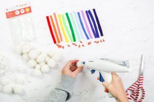 adding hot glue to white pom pom