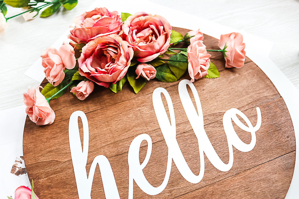 using hot glue to secure pink roses on a wood round