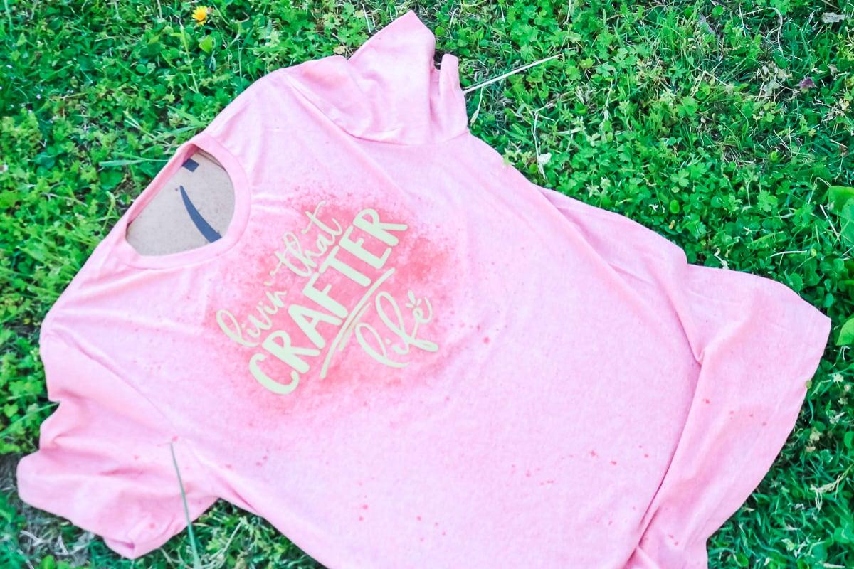 spraying bleach on vinyl on a shirt