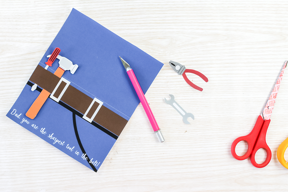 using a knife to put holes in a father's day card