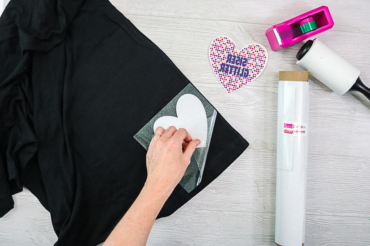 applying sister glitter htv to a black shirt