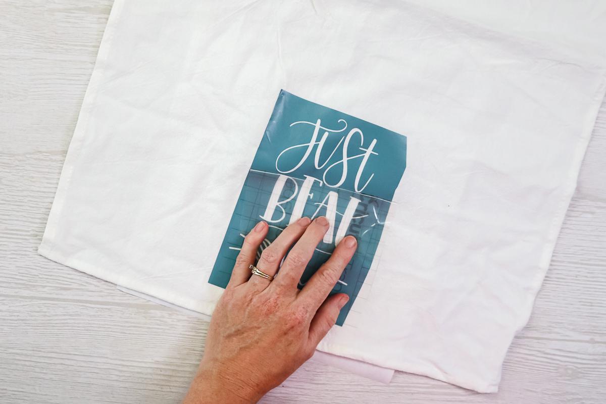 applying a vinyl stencil cut on a cricut to a tea towel